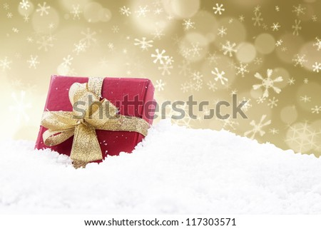 A red christmas gift with golden defocused lights background - stock photo