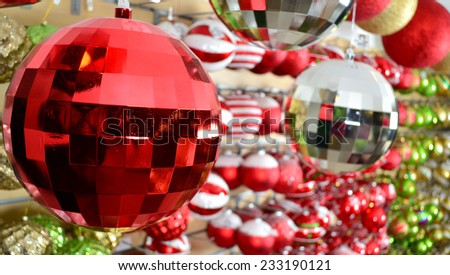 A red christmas ornament hanging from a tree with golden lighting with bokeh in the background. - stock photo