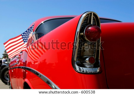 A red classic car with American flag. - stock photo