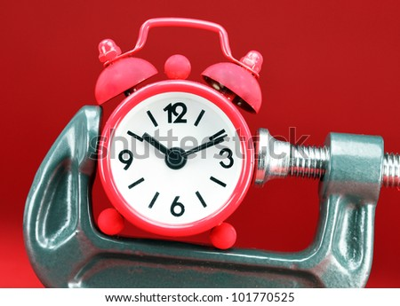 A red colored  alarm clock placed in a Grey clamp against a red background, asking the question do you manage your time effectively. - stock photo