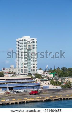 A red construction crane in front of a San Juan, Puerto Rico high rise condo building - stock photo