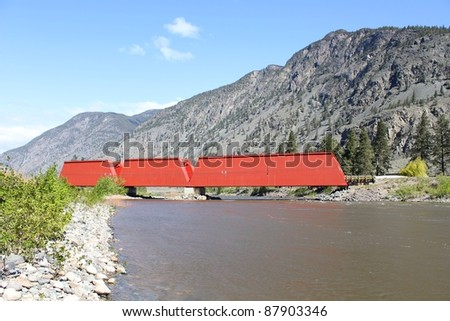A red, covered bridge which crosses the Similkameen River near Keremeos. Originally a rail bridge built in 1907, it is now a highway bridge leading to the Ashnola Valley. British Columbia, Canada. - stock photo