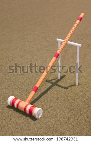 A red croquet mallet resting against a hoop - stock photo