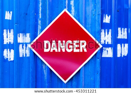 A red Danger sign mounted to a blue metal construction site wall.
