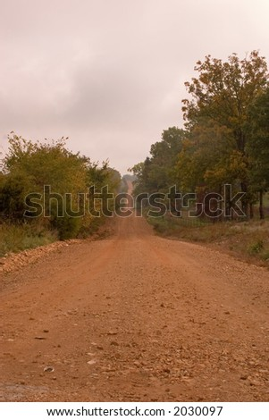 A red dirt road in rural Arkansas USA - stock photo