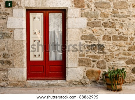 a red door in a stone house, wall and a flowerpot - stock photo