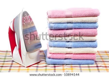 A red electric iron and multicolored towels stacked on squared mat - stock photo