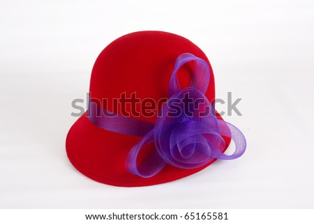 A red felt hat with a purple ribbon isolated on a white background. - stock photo