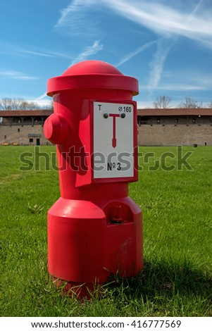 A red fire hydrant on the green grass against the blue sky. - stock photo