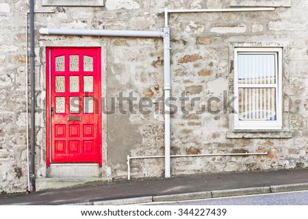 A red front door in a stone cottage in Scotland - stock photo