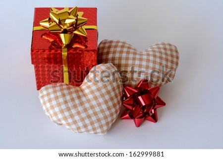 A red gift box, two hearts and white background