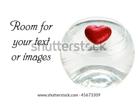 a red glittery valentines day heart floats in water in a fish bowl - stock photo