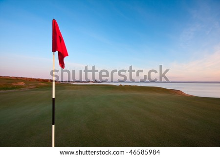 A red golf flag on a green in warm dawn light. Photo taken on the Castle Course in St Andrews, Scotland. Blue sky and the town in the background.
