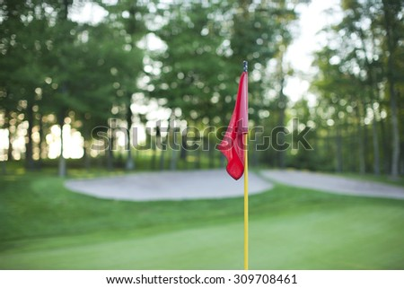 A red golf pin flag in front of a defocused green with sand traps and trees - stock photo
