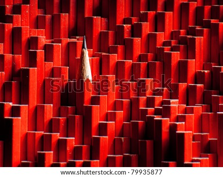 A red graphite pencil sticking out of a large group of blunt pencils. - stock photo