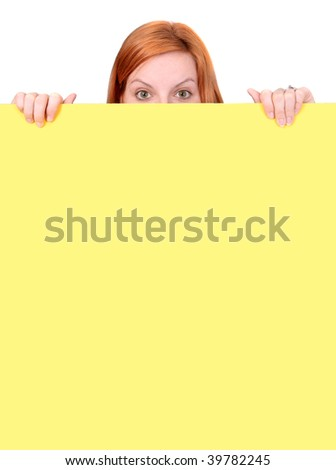 A red-haired woman peeks over the top of a yellow wall, with only her fingers and the top half of her head visible. Vertical format. - stock photo