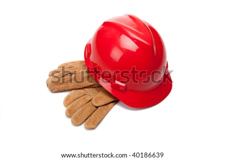 A red hard hat and leather work gloves on a white background - stock photo
