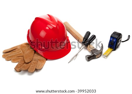 A red hard hat and leather work gloves with tools including a hammer, screwdrivers and a tape measuring a white background - stock photo
