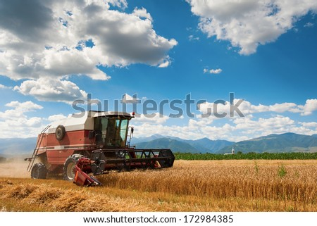 A red harvester in work with mountains in background - stock photo