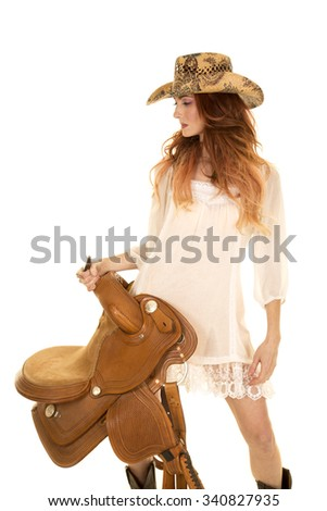 A red head cowgirl holding onto her saddle looking to the side in her sheer white dress. - stock photo