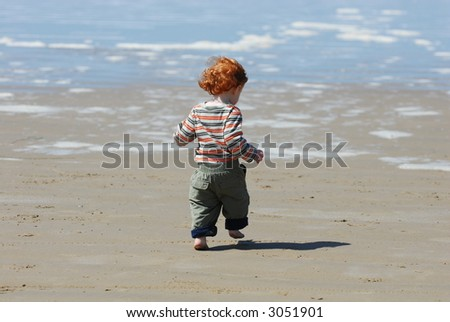 A red headed toddler runs and plays on the beach.