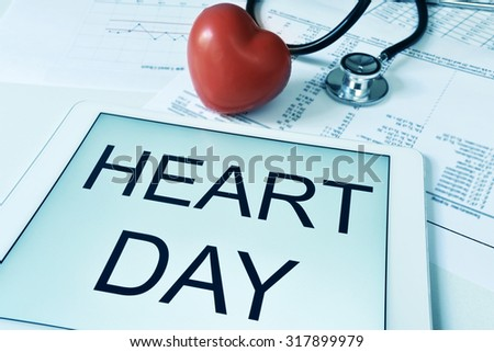 a red heart, a stethoscope and a tablet computer with the text heart day in its screen, with a filter effect - stock photo