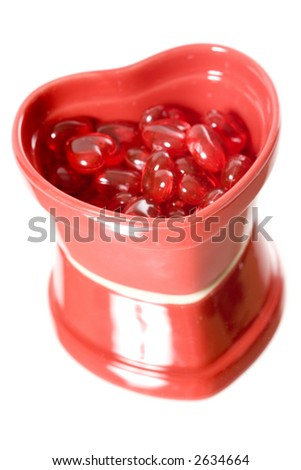 A red heart dish filled with miniature hearts - stock photo