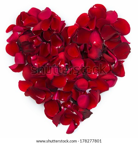 A red heart is formed by rose petals. - stock photo