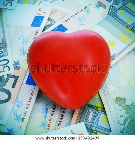 a red heart on a pile euro banknotes depicting the idea of love for the money or the cost of love or the cost of the cardiovascular diseases for the healthcare system - stock photo