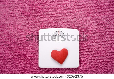 A red heart placed on scales, shot landscape. - stock photo