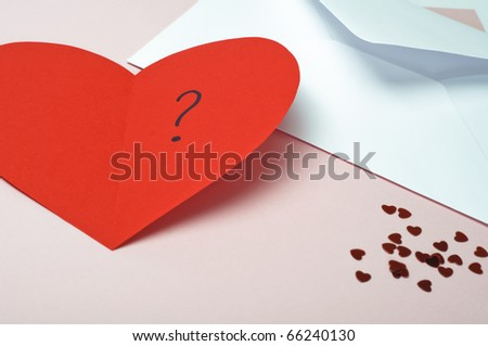 A red heart-shaped Valentines card, opened to reveal a question mark.  Small metallic hearts scattered at bottom right, with white open envelope at top right.  Pink background with copy space. - stock photo