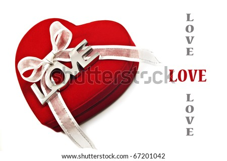 a Red heart with the word love spelled out in silver on a white ribbon - can be used for Valentine's day