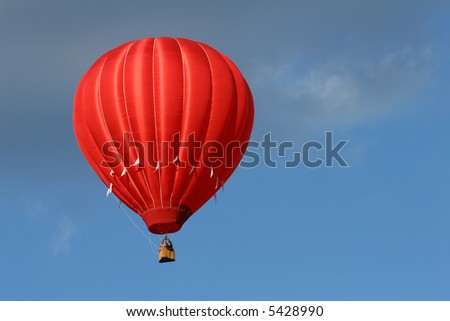 a red hot air balloon in a cloudy blue sky - stock photo