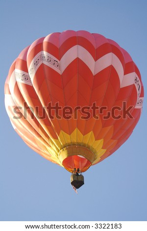 A Red Hot Air Balloon Lifts Off into the Clear Blue Morning Sky - stock photo