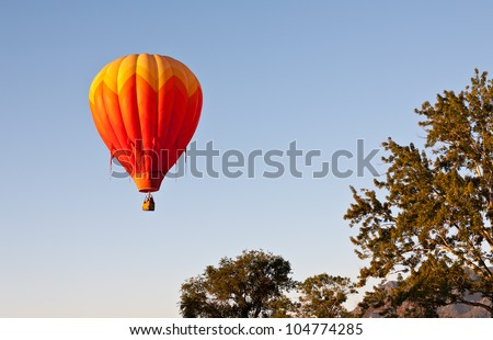 A red hot air balloon rises above the treetops during Colorado's Balloon Classic - stock photo