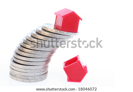 A red house on a slanting stack of coins. Below one house that already fell. Symbolizes uncertainty about the real estate market.