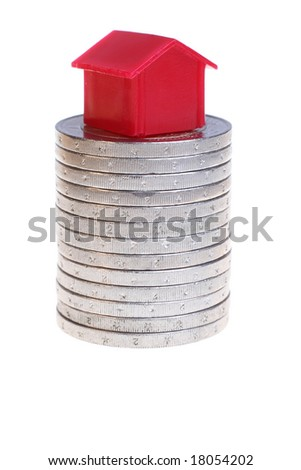 A red house on a stack of coins. Isolated on white. Symbolizes a risky investment in real estate.