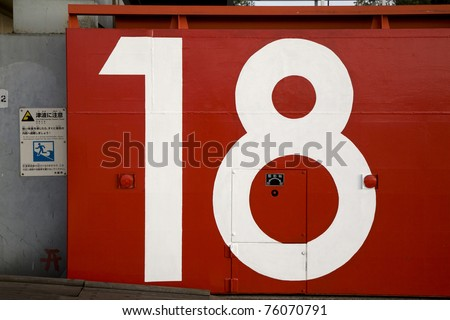 a red japanese tsunami watertight door in osaka bay area with the number 18 painted on it - stock photo