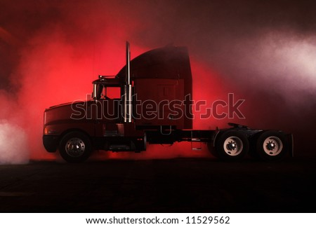 A red Kenwood truck with chrome exhaust pipes and smoke. - stock photo