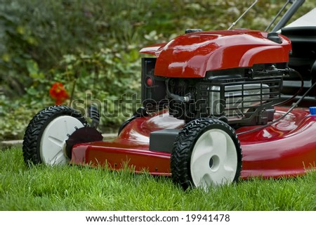 A red lawnmower on the lawn in the garden. - stock photo