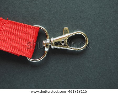 A red leash with snap hook over black background