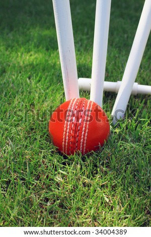 A red leather cricket ball lying in green grass at the base of three white wooden cricket stumps. Set on a portrait format.