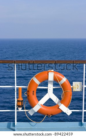 A red lifebuoy in front of the blue sea - stock photo