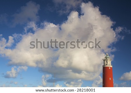 a red lighthouse with a dramatic blue sky with white clouds in summer - stock photo