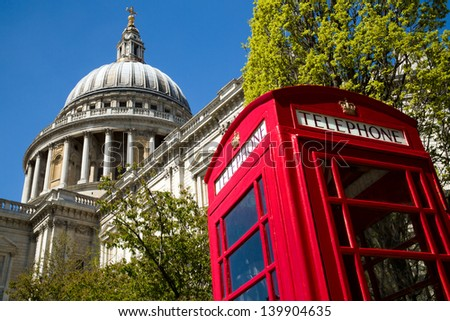 A red London phone box with the dome of St Paul's Cathedral in the background