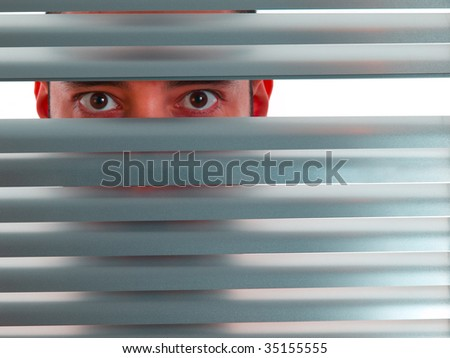 A red man looks to the camera through the blinds. - stock photo