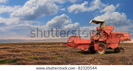 A red old combine harvester in a wheat field - stock photo