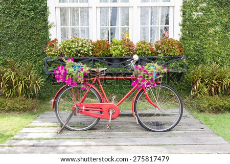 A red old vintage bicycle standing in front of vintage wall - stock photo