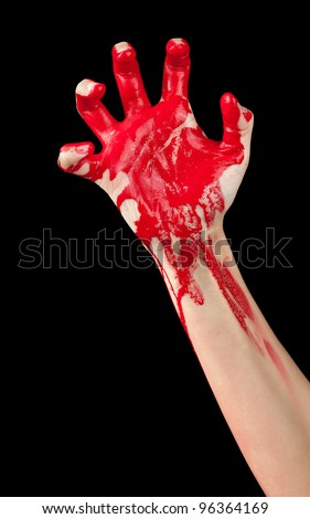 A red paint covered hand clenching isolated on black.