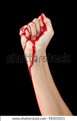 A red paint soaked hand making a fist isolated on black. - stock photo